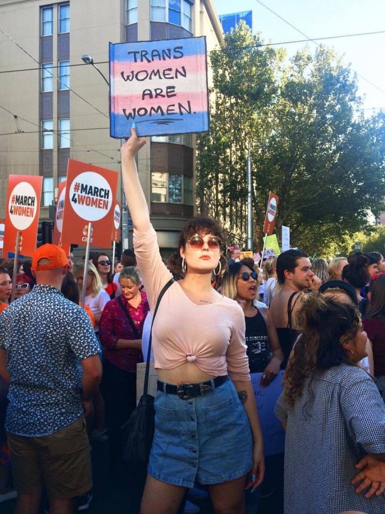 Lana Faye holding a 'trans women are women' sign to TERFs