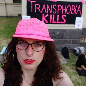 the writer in front of transphobia kills banner