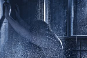 A male figure presses their hands onto the wall of the shower