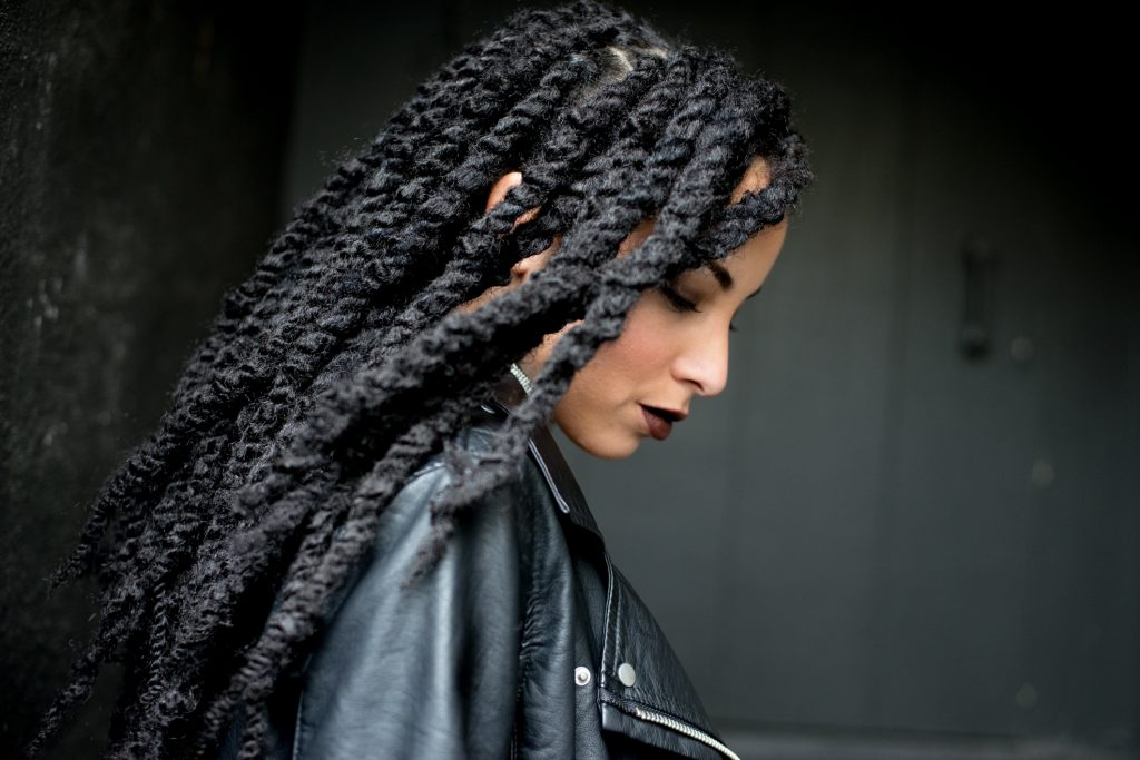 a black woman flips her hair dreads