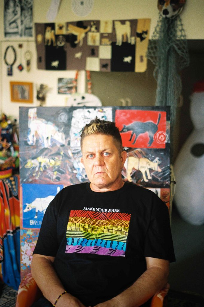 Peter Waples-Crowe facing the camera wearing a black tshirt with a rainbow Indigenous artwork on the chest and the words 'make your mark'