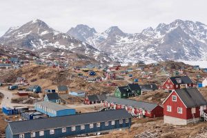 The town of Tasiilaq, Greenland, is in the foreground, with a mountainous landscape in the background. The town is dotted with colourful buildings.