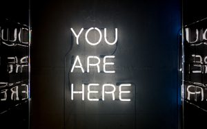 "A white neon sign reads ""you are here"" all in upper case against a dark background."