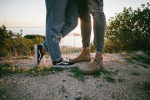 Two people stand on a beach at sunset with their legs intertwined. The image only shows them from their legs down, and they are wearing jeans and casual shoes.