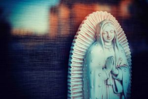 A white marble Virgin Mary statue is pictured praying.