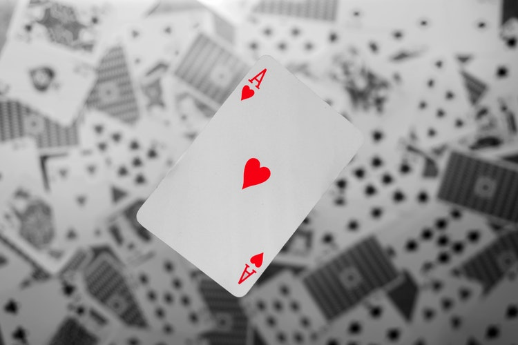 An ace of hearts playing card in colour on top of a pile of cards