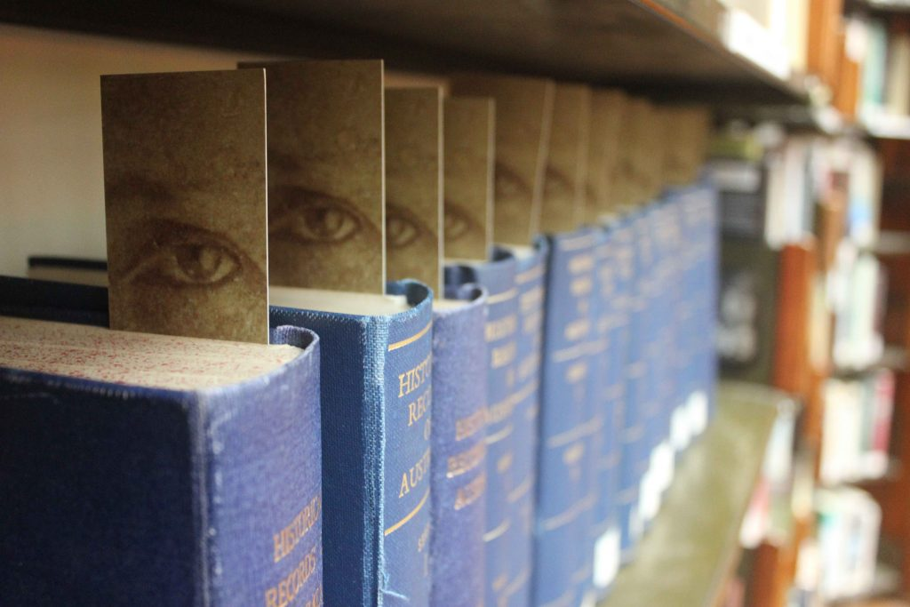 A row of blue books each have a bookmark with an eye on it sticking out the top of the book.