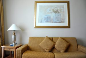 A camel coloured couch with two matching pillows sits in front of a beige wall with a portrait of flowers on it. A tabled with a lamp is on the left.