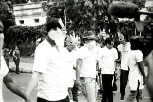 in a black and white image, a group of people march wearing feathery masks and scarves over their mouths to hide their identities.