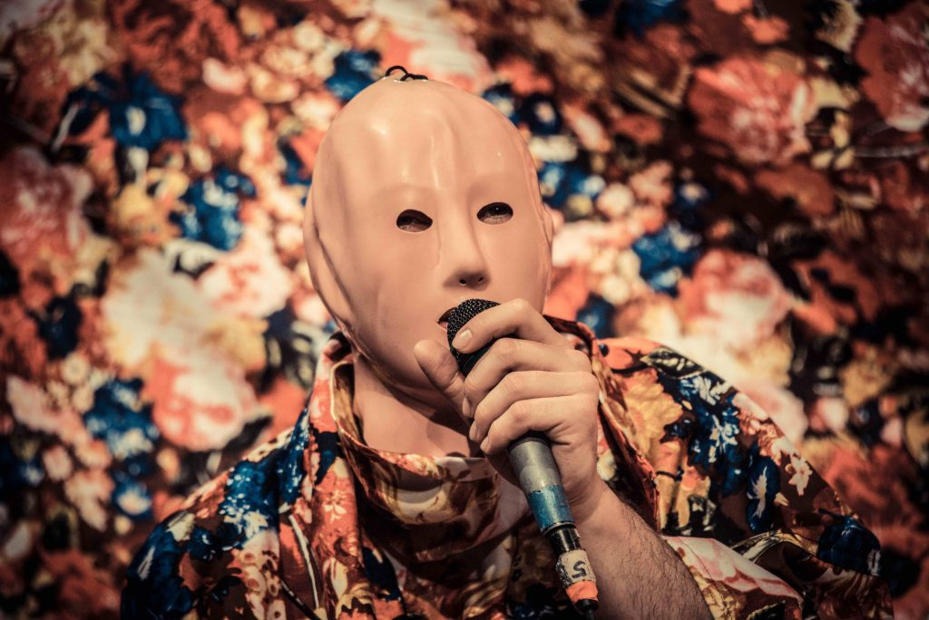 a person in a mask holds a microphone to their mouth