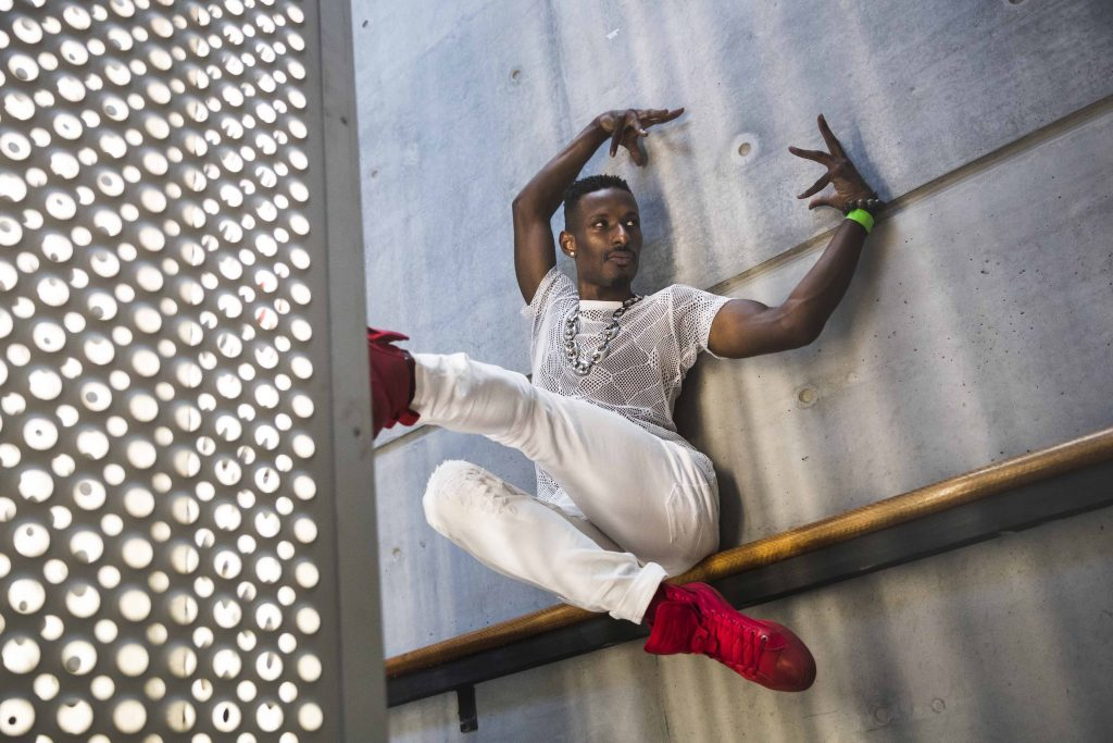 Dashaun Wesley wears all white with red shoes, posing with his hands up and foot against a wall.
