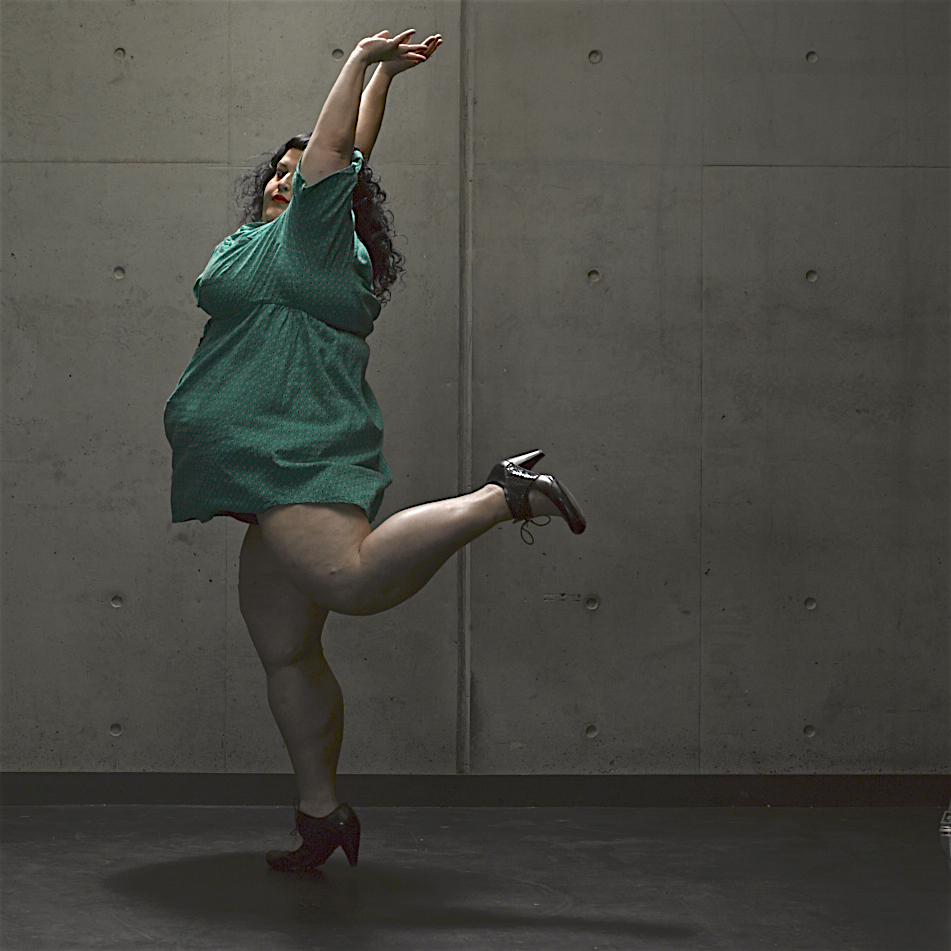 Kelli Jean wears a short green dress, and has their hands above their head with one leg kicked behind them.