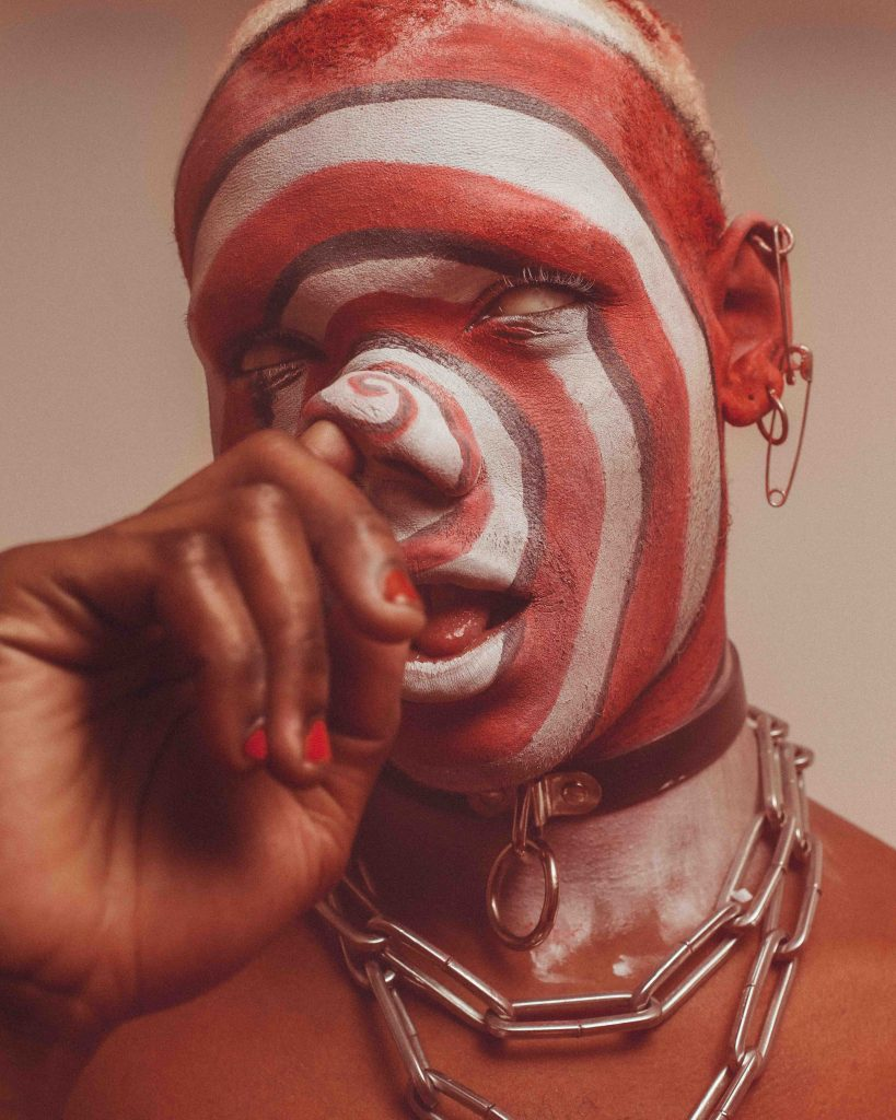 a person has their face painted with red and white circles, the whites of their eyes visible, and their hand touching their nose.