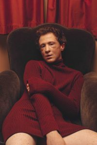 Sam Stoich sits in a comfy couch, facing the camera, wearing only a maroon jumper.