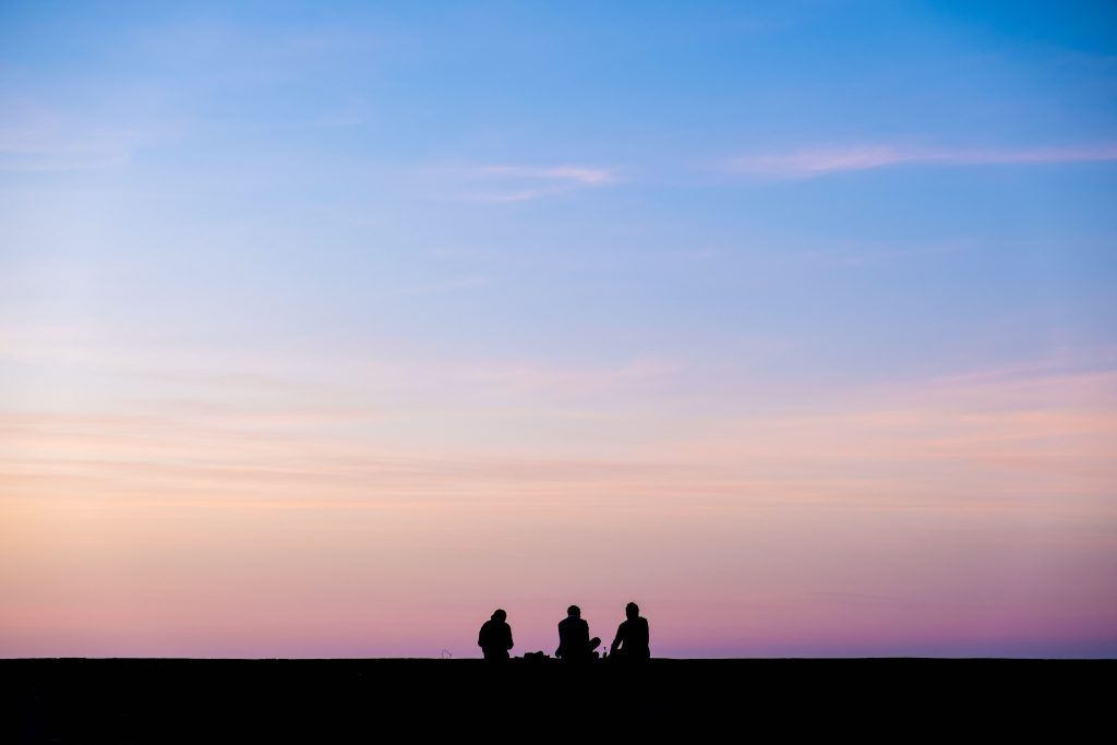 Silhouette photography of three people in front of a sunset