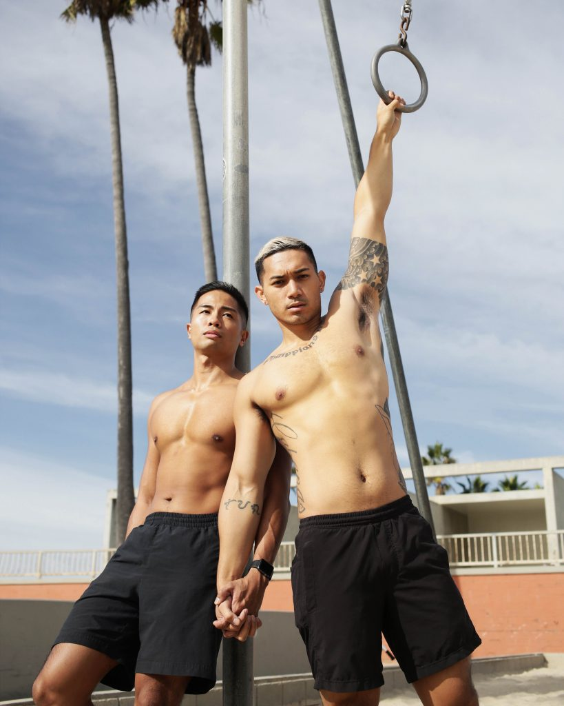 two shirtless people stand, facing the camera among outdoor gym equipment. One of them is holding a gym ring above their head.