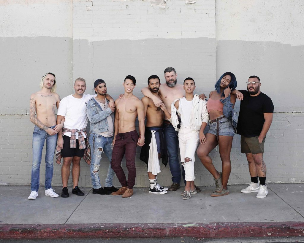 A group of people of different sizes and races stand facing the camera. Some are shirtless, some are clothed.