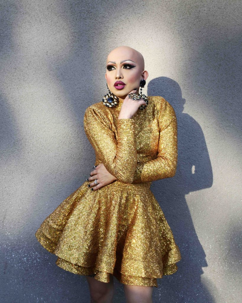 A person with no hair, a full face of makeup and a sparkly gold dress looks to the side in front of a concrete backdrop.