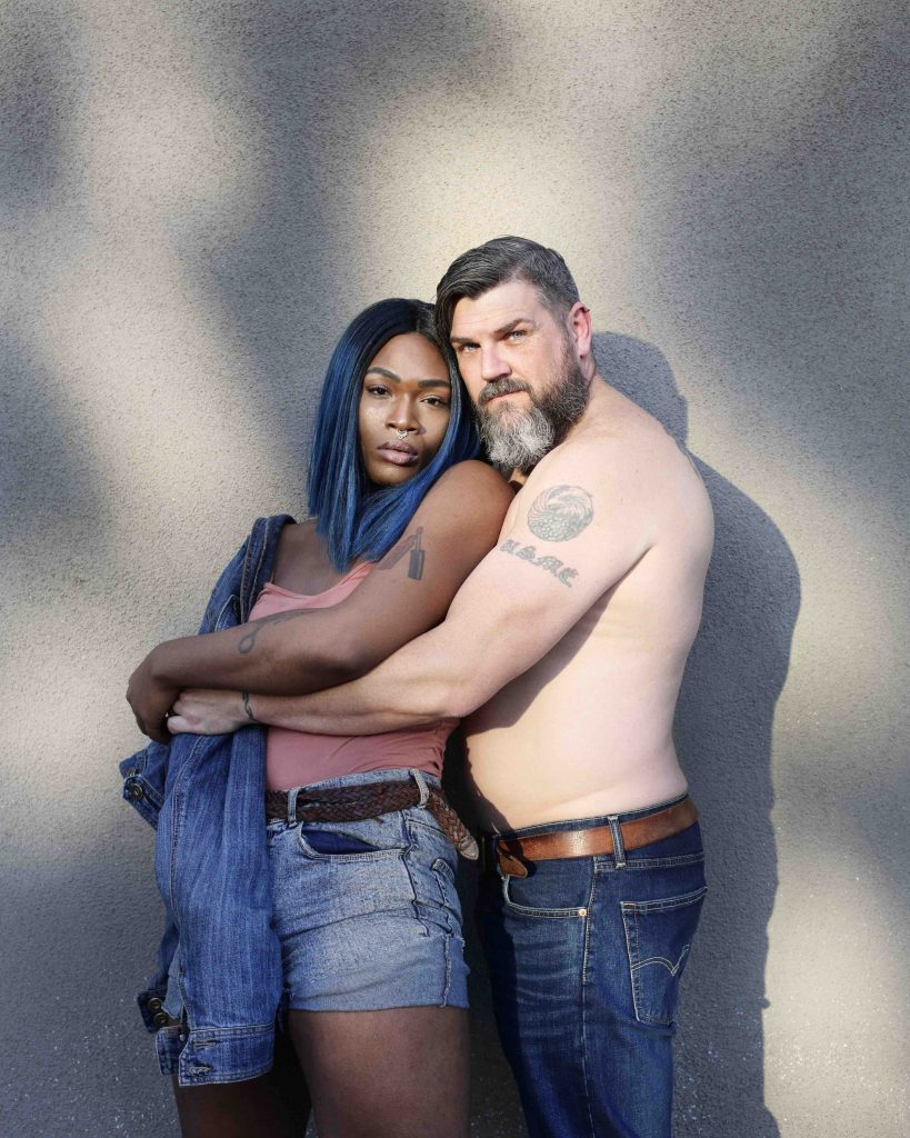 Two people stand, spooning, facing the camera. One is shirtless with a beard and tattoos, while the other has blue and black shoulder length hair and tattoos, and is wearing a singlet and shorts.