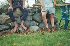 Two people sit on a rock wall. They are only shown waist down.