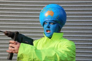 A person with a globe on their head and a blue face to match the colour of the ocean wears a high vis jacket and holds a drill