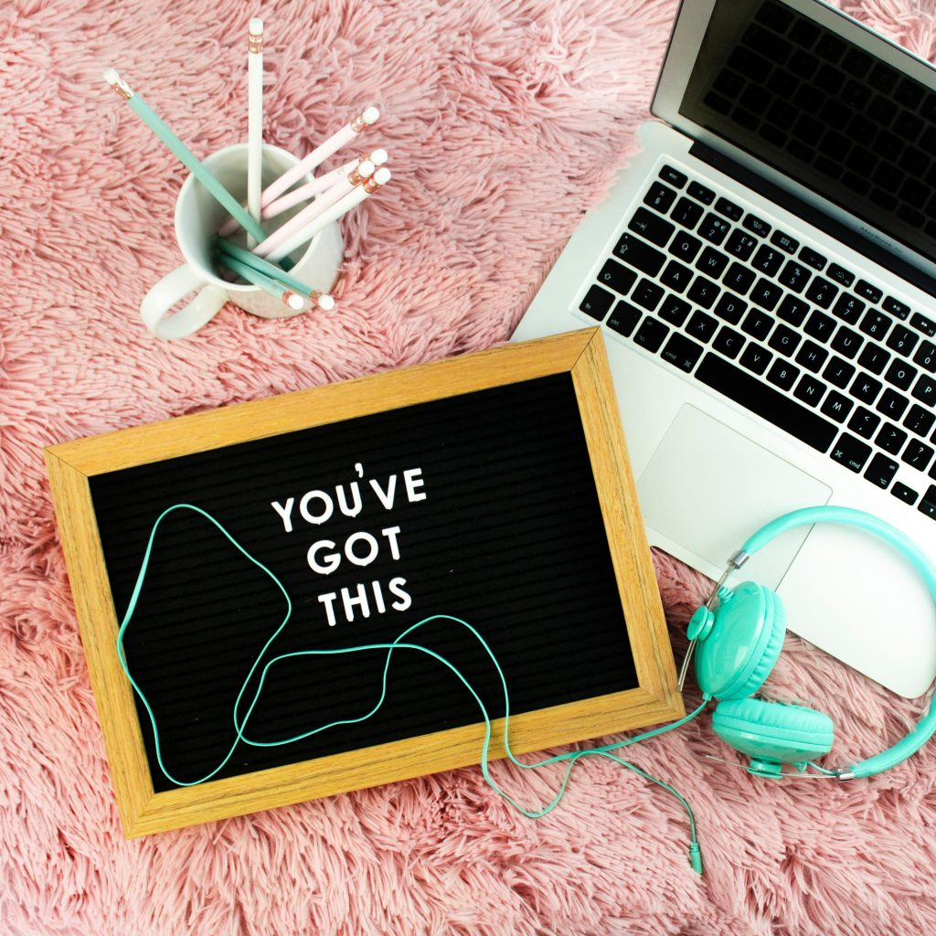 A laptop, turquoise headphones, a sign saying 'you've got this' and a cup of pencils