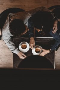 Two people having coffee and hugging, shown from above