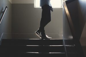 a person stands at the top of a staircase. The person is visible from the waist down.