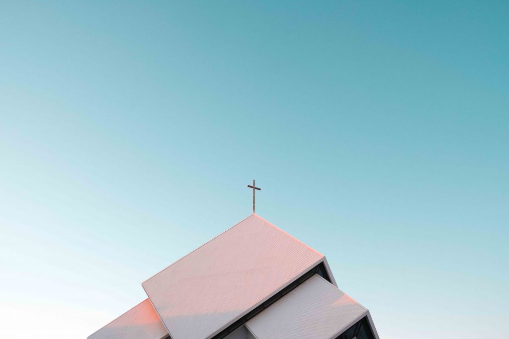 A cross sits on top of a white building.