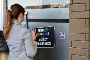 "Person with long hair wearing a blazer places a leaflet on the fridge. The leaflet says ""respect existence (in rainbow font) or expect resistance."""