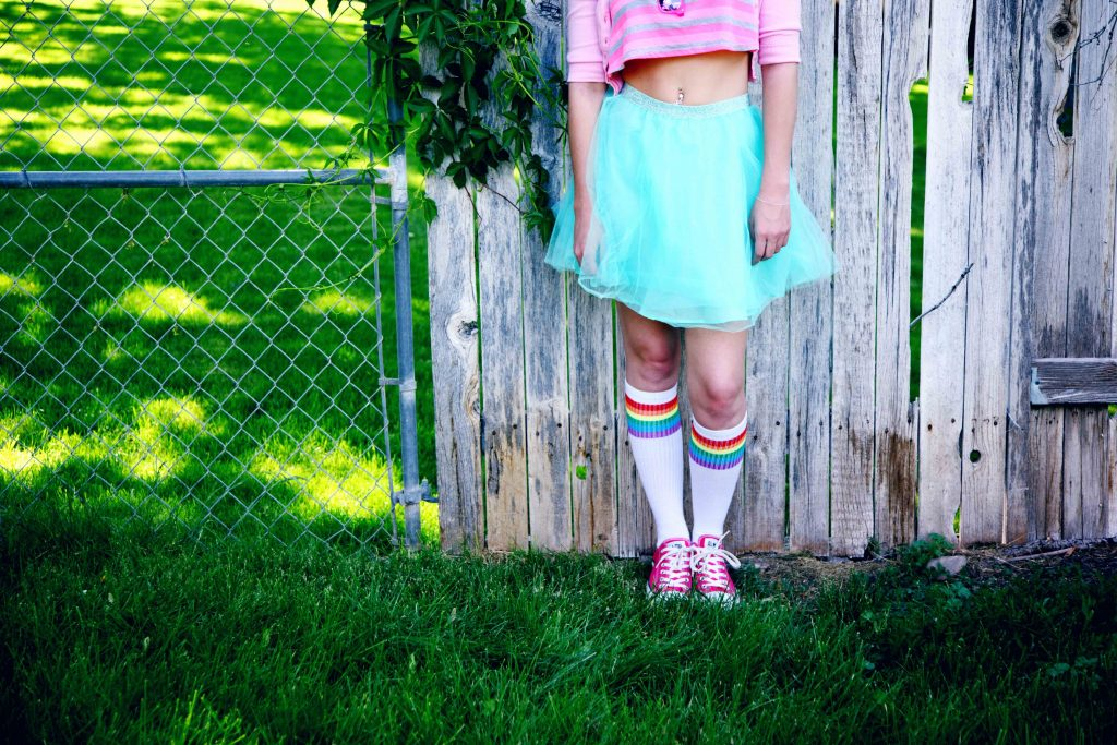Portrait of a young person standing against a wooden fence wearing rainbow, blue and pink for Pride.