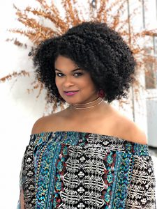 Raquel Willis faces the camera, standing in front of a plant.