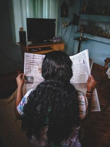 Person with long curly hair reading the newspaper