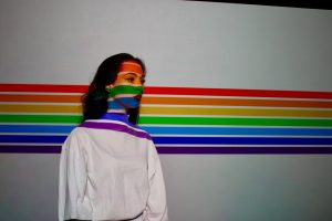 Person standing in front of a white wall with rainbow stripes running horizontally across them and the wall