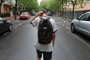 a young adult stands with their back to the camera wearing a backpack, running a hand through their hair.