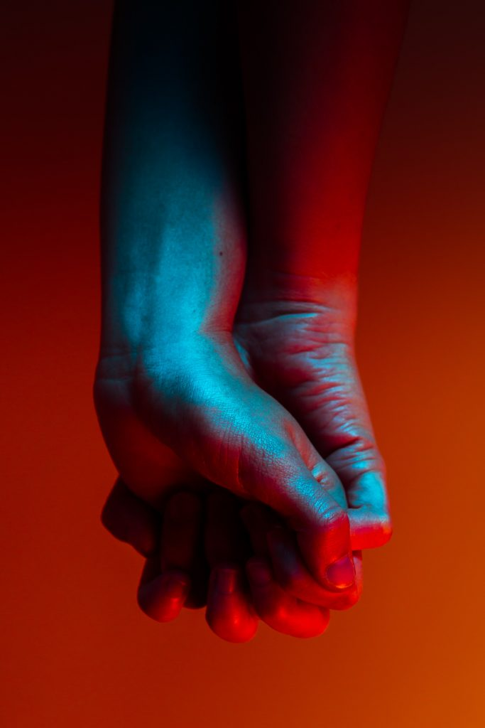 two hands clasped together in red and blue light