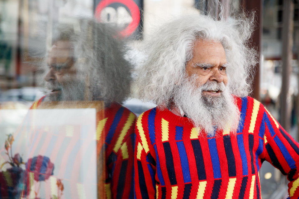 Jack Charles wears a colourful jumper, and looks to the right of the frame