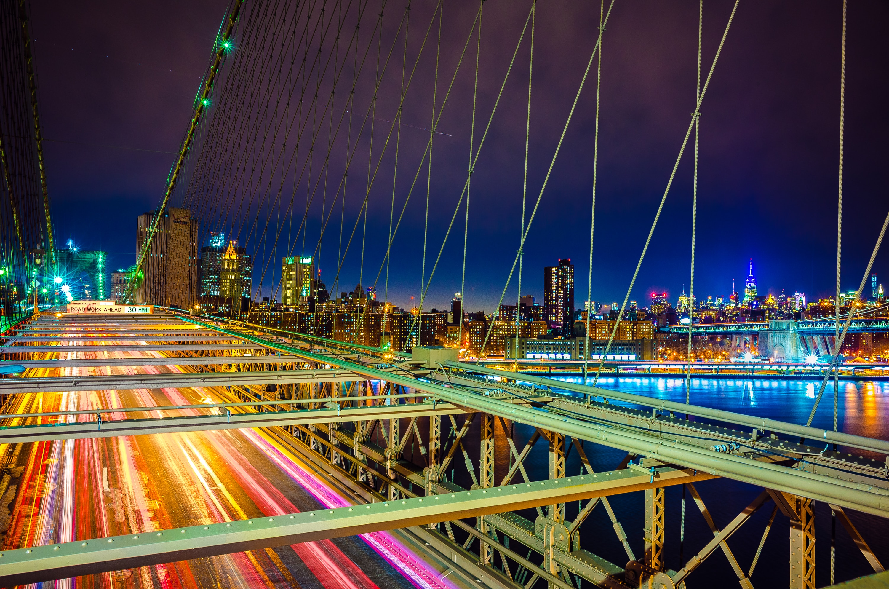Brooklyn Bridge at night with city lights showing