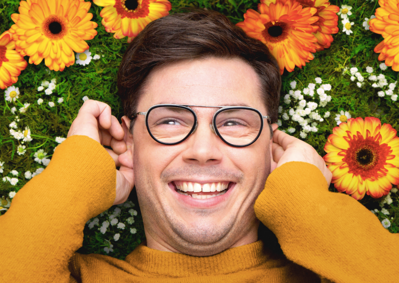 Person wearing glasses and a mustard yellow top smiles in front of a background of flowers and greenery