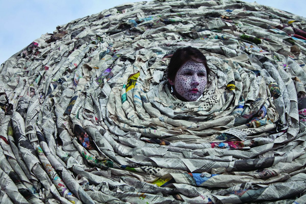 A face in the centre of a large spiral made of newspaper