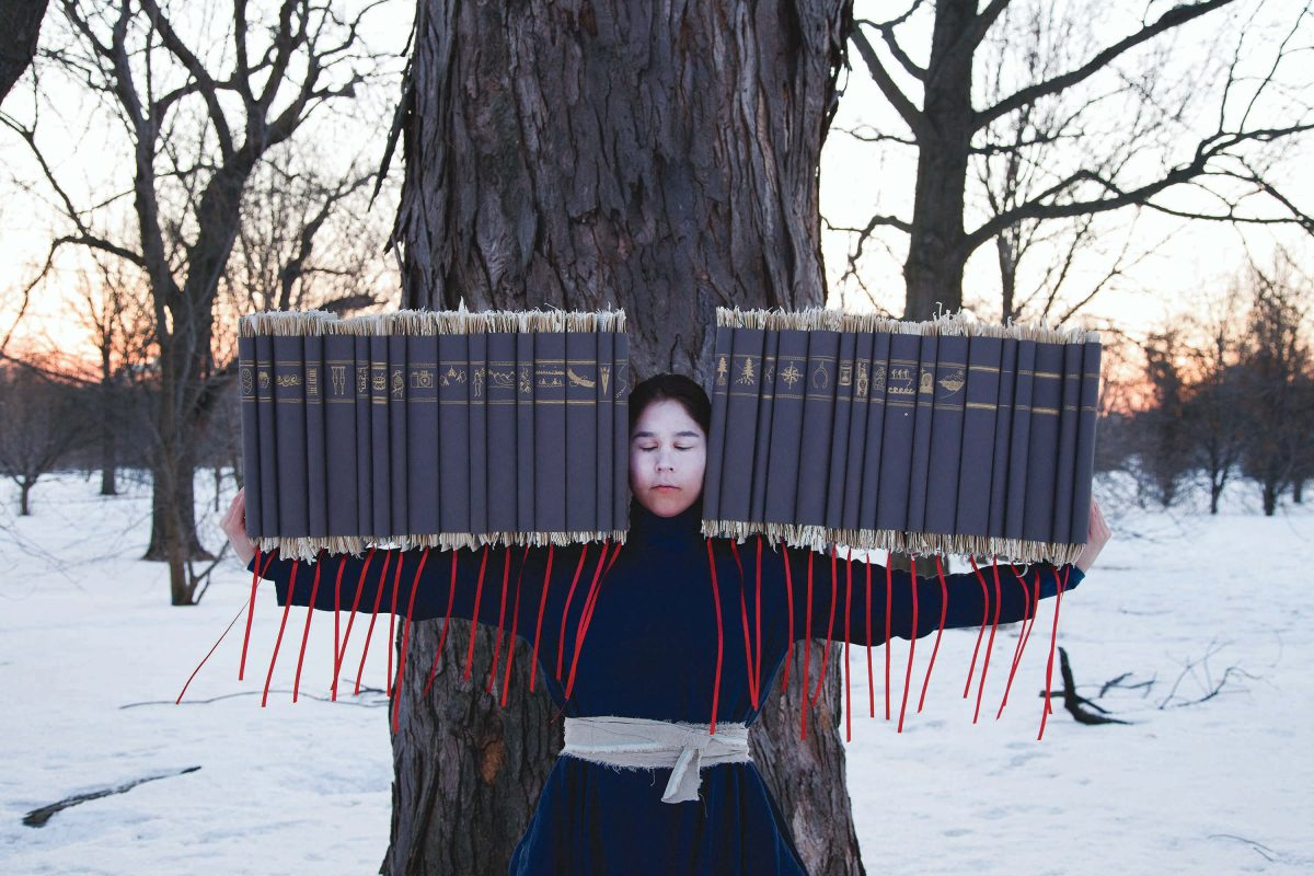Person holds objects with string hanging down from them in front of a tree