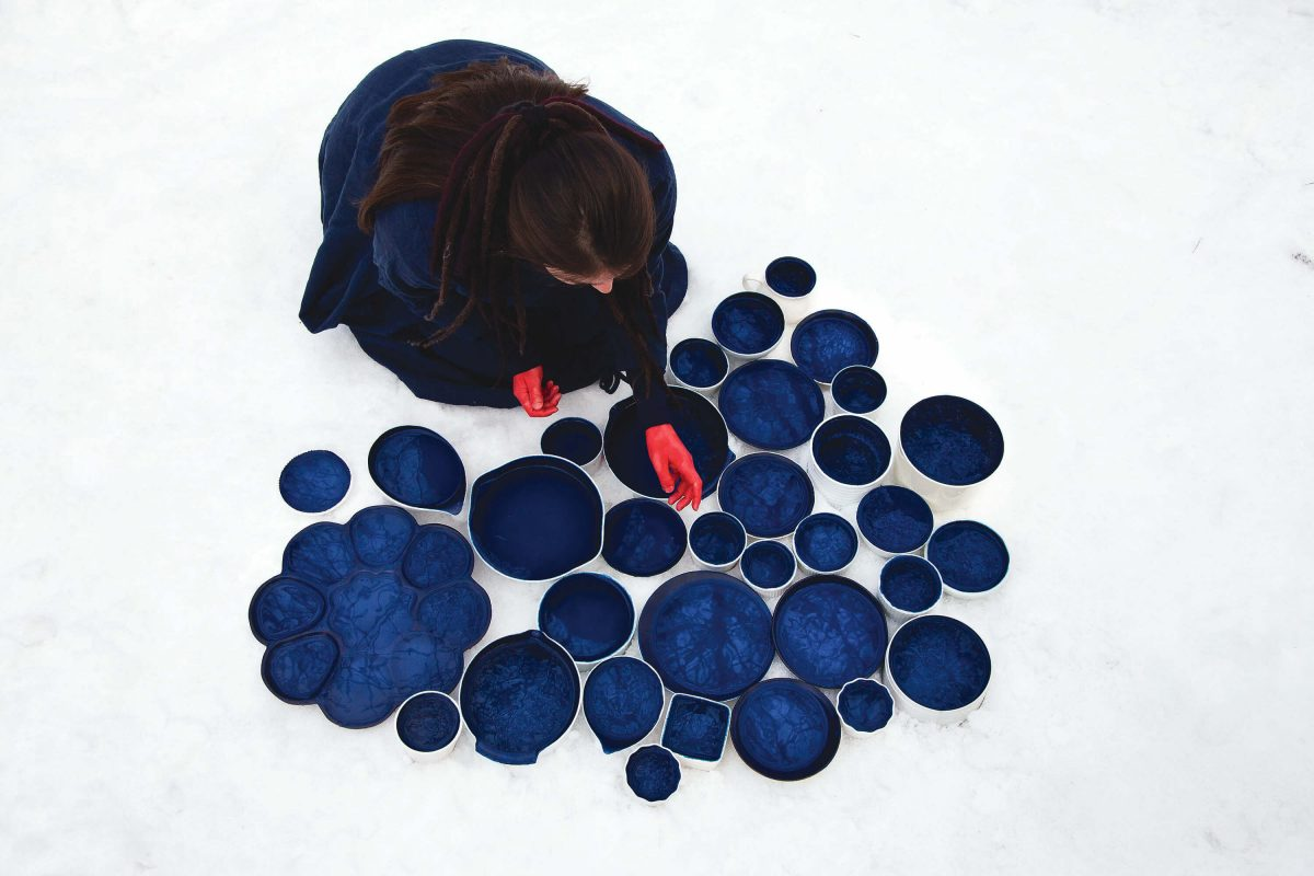 Person with long hair and red hands leans over blue circular objects