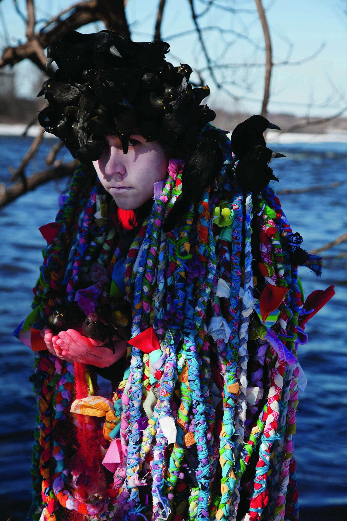 Person wearing brightly colour long woven threads holds birds in their hands and on their head