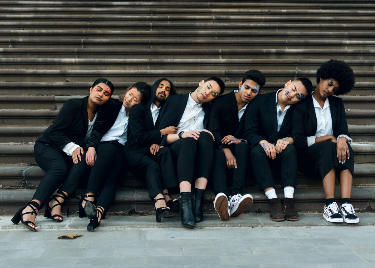 A group of Asian models sit at the bottom of a flight of steps, leaning their heads to the left