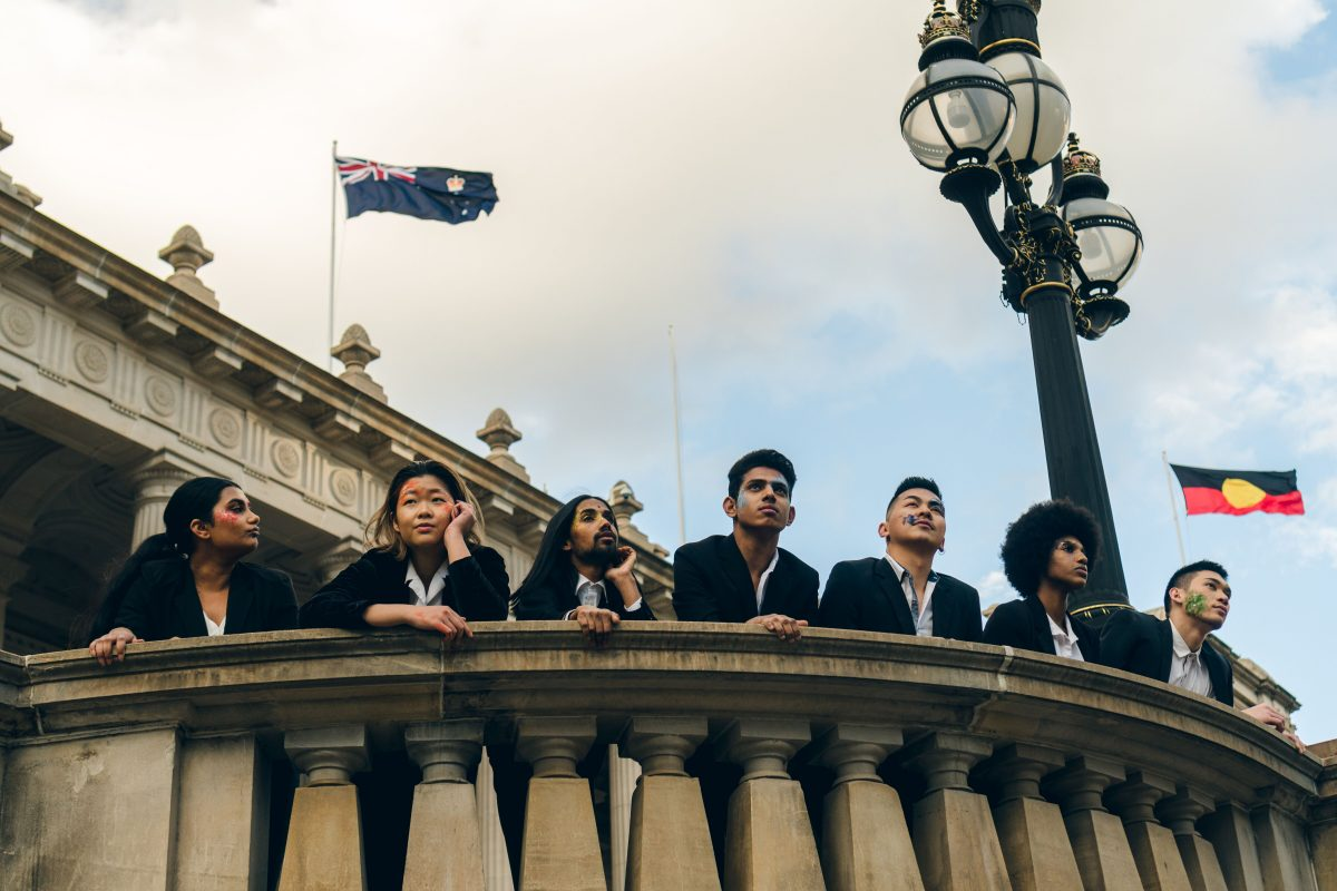 A group looks out off a balcony, with the Australian flag and Aboriginal flag behind them