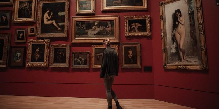person standing in front of paintings in museum