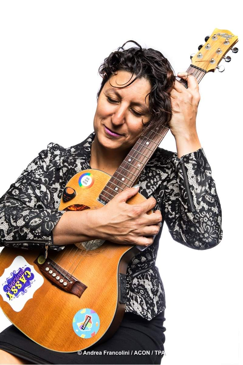 A woman holds a guitar into her chest and smiles with eyes closed