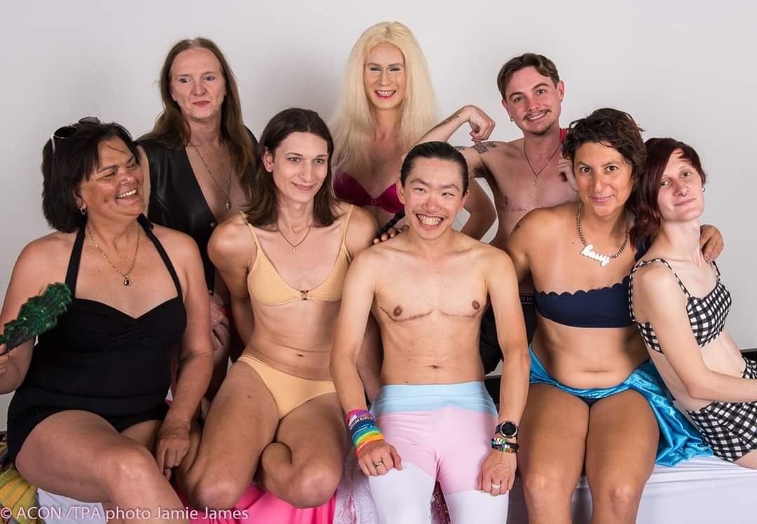 A group of trans people in bathing suits sit smiling together