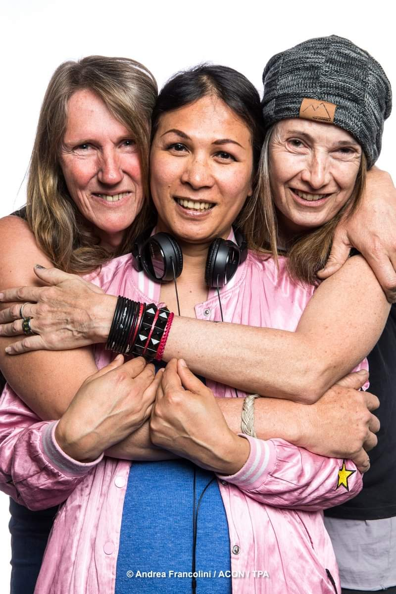 Three smiling women embrace side by side
