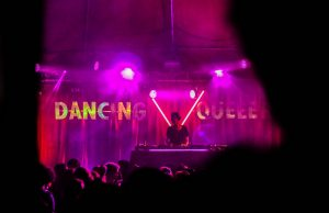 Pink lighting at a nightclub with the words 'DANCING QUEEN' hanging on the wall